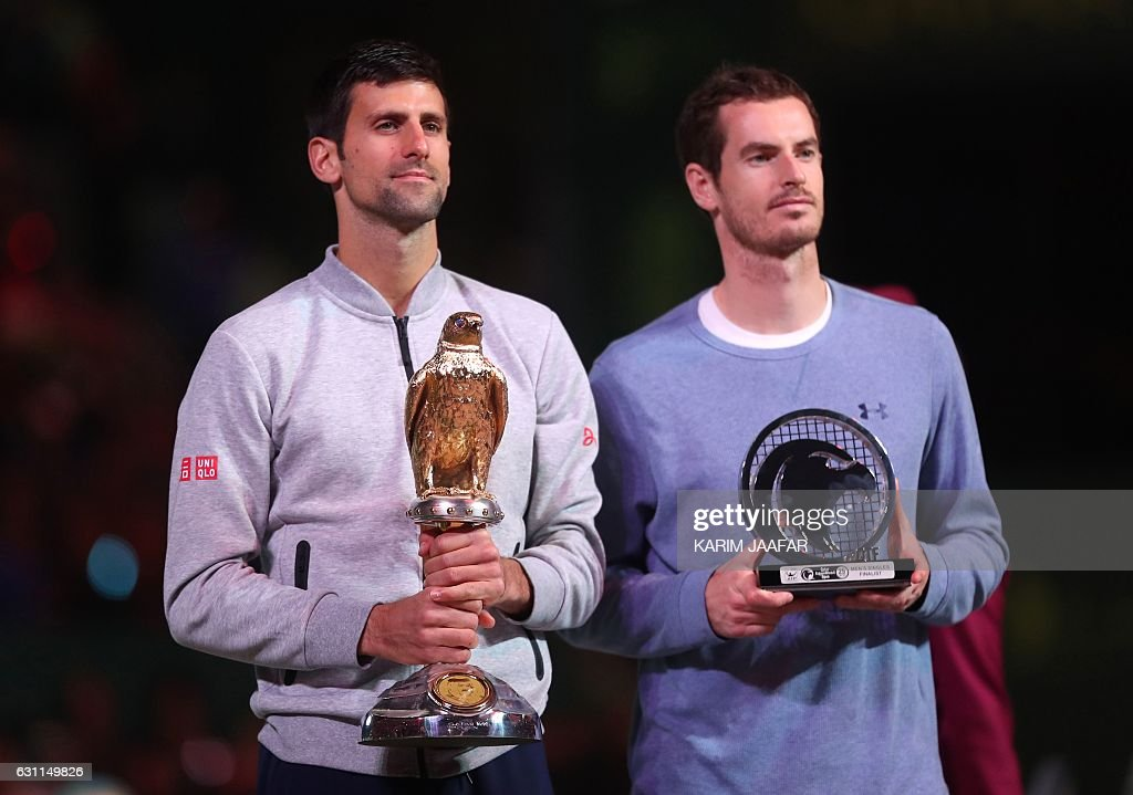 Serbia's Novak Djokovic (L) poses with the winner's trophy after beating Britain's Andy Murray during their final tennis match at the ATP Qatar Open in Doha on January 7, 2017. / AFP / KARIM