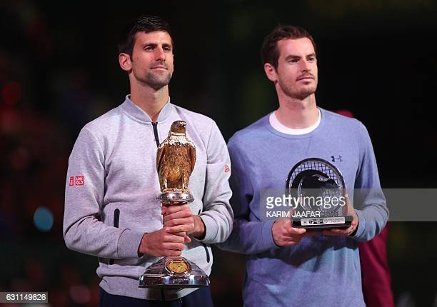 Serbia's Novak Djokovic poses with the winner's trophy after beating Britain's Andy Murray during their final tennis match at the ATP Qatar Open in...