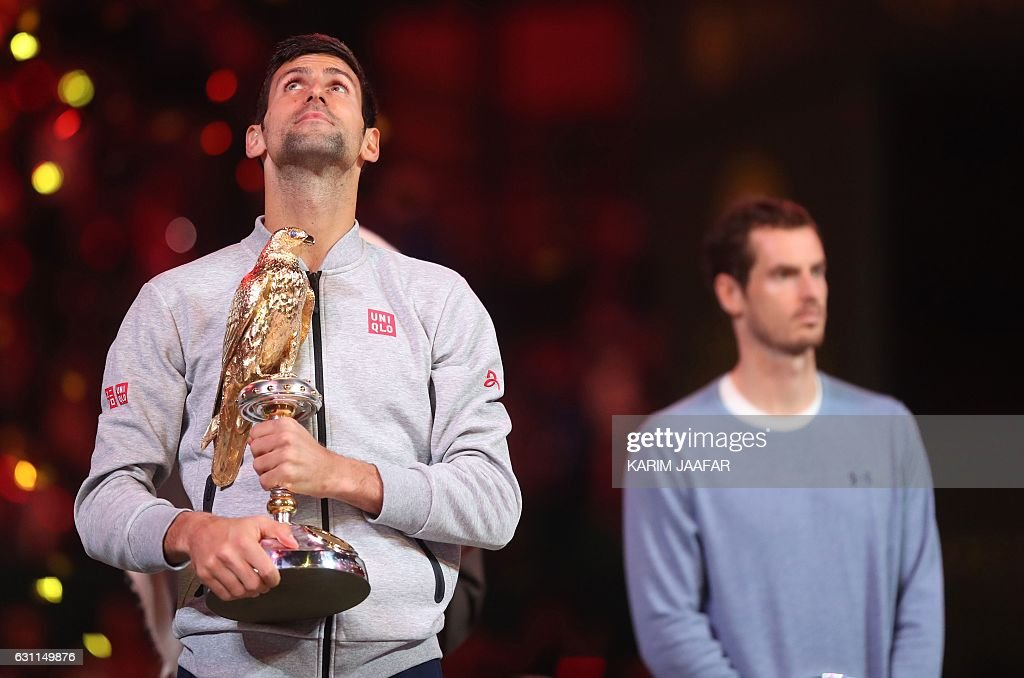 TOPSHOT - Serbia's Novak Djokovic (L) poses with the winner's trophy after beating Britain's Andy Murray during their final tennis match at the ATP Qatar Open in Doha on January 7, 2017. / AFP / KARIM