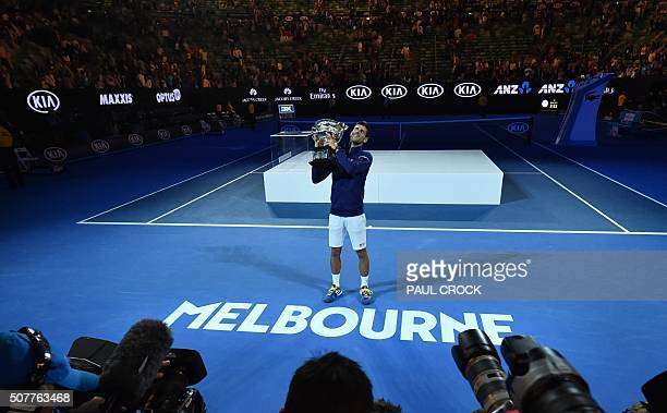 Serbia's Novak Djokovic poses with the winner's trophy after defeating Britain's Andy Murray in their men's singles final match on day fourteen of...