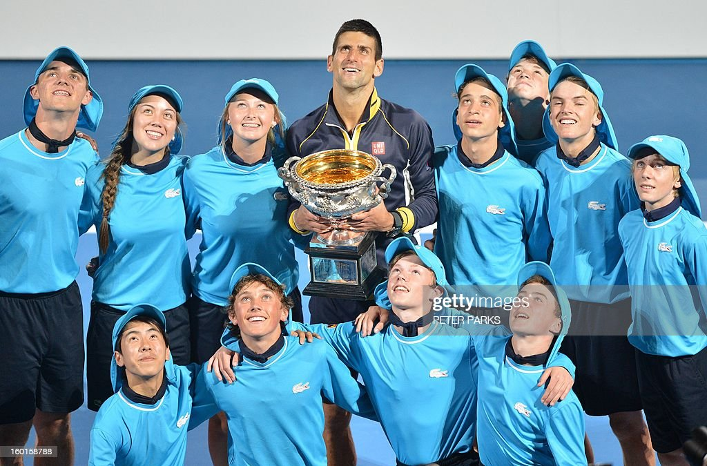 Serbia's Novak Djokovic poses with the winners trophy and ball children after his victory over Britain's Andy Murray during the men's singles final on day 14 of the Australian Open tennis tournament in Melbourne on January 27, 2013.