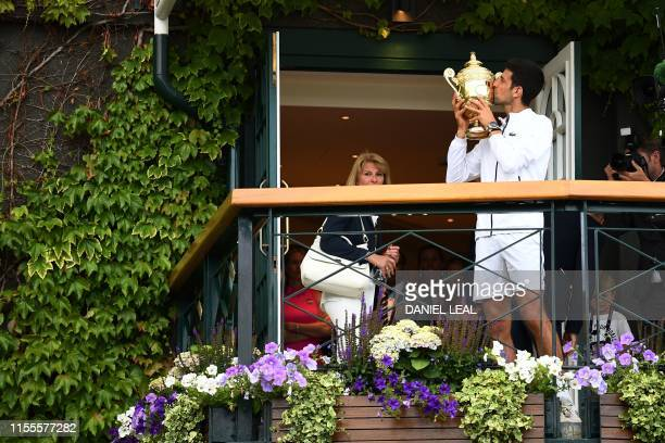 Serbia's Novak Djokovic poses with the winner's trophy on the balcony of the club house after beating Switzerland's Roger Federer during their men's...