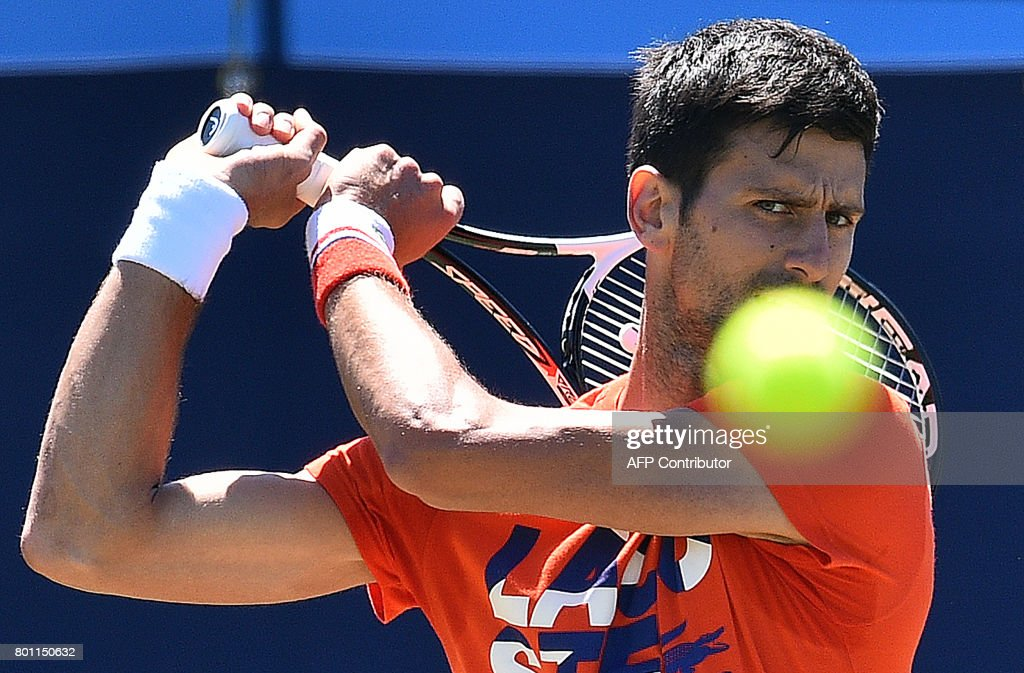 TOPSHOT - Serbia's Novak Djokovic practices ahead of his men's singles tennis match at the the ATP Aegon International tennis tournament in Eastbourne, southern England, on June 26, 2017. /