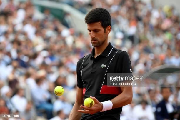 Serbia's Novak Djokovic prepares to serve to Italy's Marco Cecchinato during their men's singles quarterfinal match on day ten of The Roland Garros...