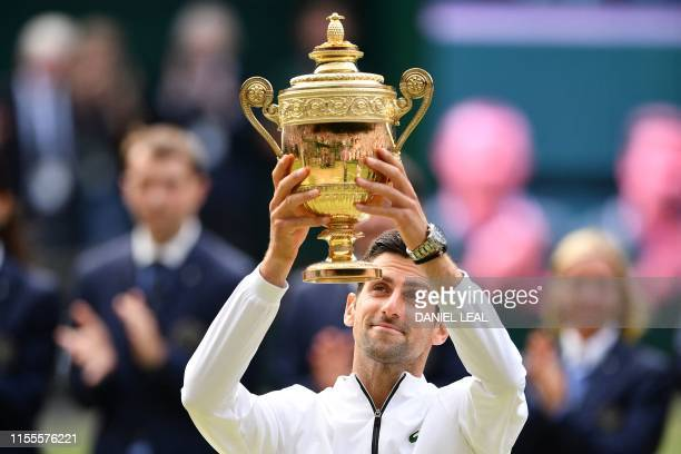 Serbia's Novak Djokovic raises the winner's trophy after beating Switzerland's Roger Federer during their men's singles final on day thirteen of the...
