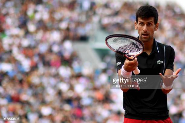 TOPSHOT Serbia's Novak Djokovic reacts after a point against Italy's Marco Cecchinato during their men's singles quarterfinal match on day ten of The...