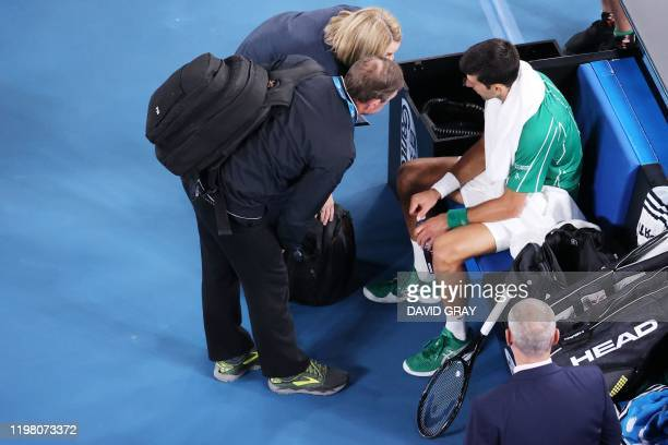Serbia's Novak Djokovic receives medical attention as he plays against Austria's Dominic Thiem during their men's singles final match on day fourteen...