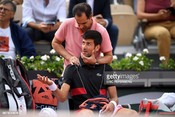 Serbia's Novak Djokovic receives medical treatment from a trainer during his men's singles quarterfinal match against Italy's Marco Cecchinato on day...