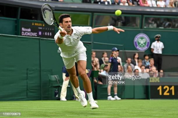 Serbia's Novak Djokovic returns against Britain's Jack Draper during their men's singles first round match on the first day of the 2021 Wimbledon...
