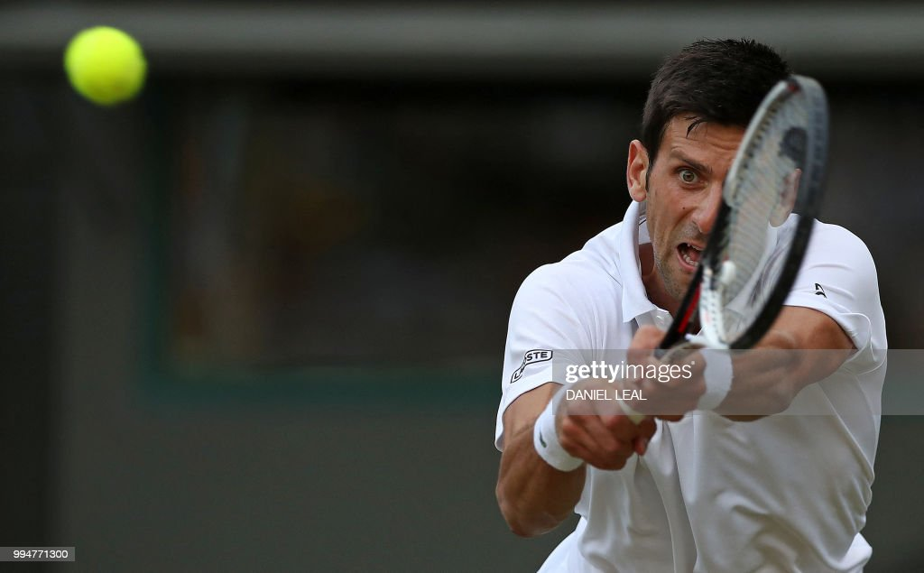 TOPSHOT - Serbia's Novak Djokovic returns against Russia's Karen Khachanov during their men's singles fourth round match on the seventh day of the 2018 Wimbledon Championships at The All England Lawn Tennis Club in Wimbledon, southwest London, on July 9, 2018. (Photo by Daniel LEAL-OLIVAS / AFP) / RESTRICTED