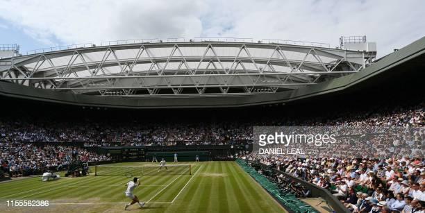 Serbia's Novak Djokovic returns against Switzerland's Roger Federer during the men's singles final on day thirteen of the 2019 Wimbledon...