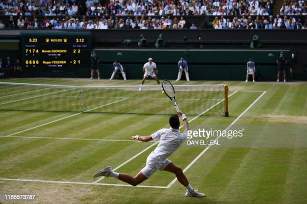 TOPSHOT Serbia's Novak Djokovic returns against Switzerland's Roger Federer during the men's singles final on day thirteen of the 2019 Wimbledon...