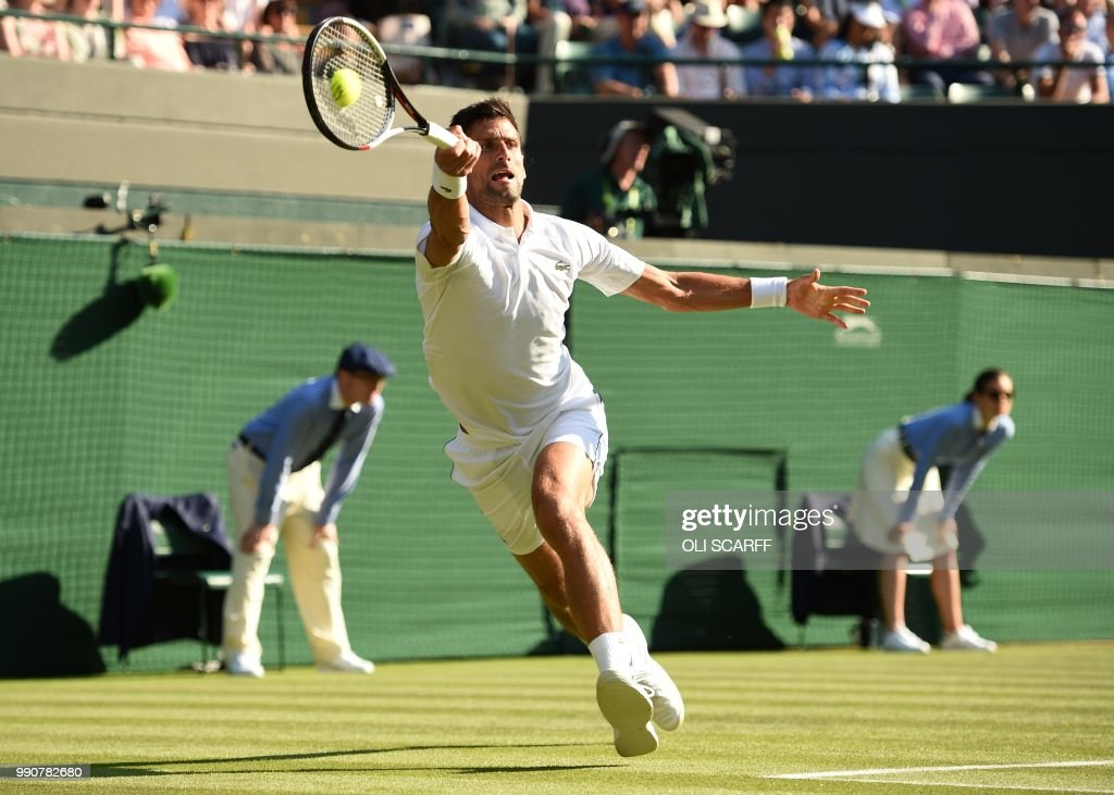 TOPSHOT - Serbia's Novak Djokovic returns against US Player Tennys Sandgren during their men's singles first round match on the second day of the 2018 Wimbledon Championships at The All England Lawn Tennis Club in Wimbledon, southwest London, on July 3, 2018. (Photo by Oli SCARFF / AFP) / RESTRICTED