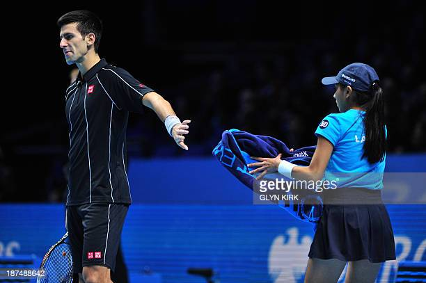 Serbia's Novak Djokovic returns his towel to the ball girl between points against France's Richard Gasquet during their group B singles match in the...