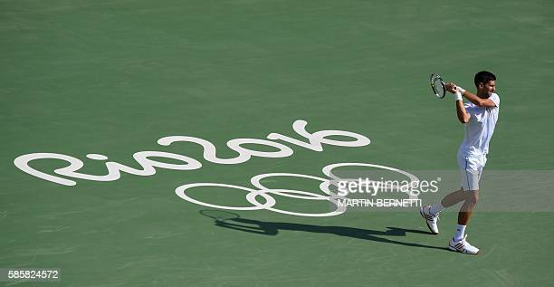 TOPSHOT Serbia's Novak Djokovic returns the ball during a training session at the Olympic Tennis Center in Rio de Janeiro on August 4 ahead of the...