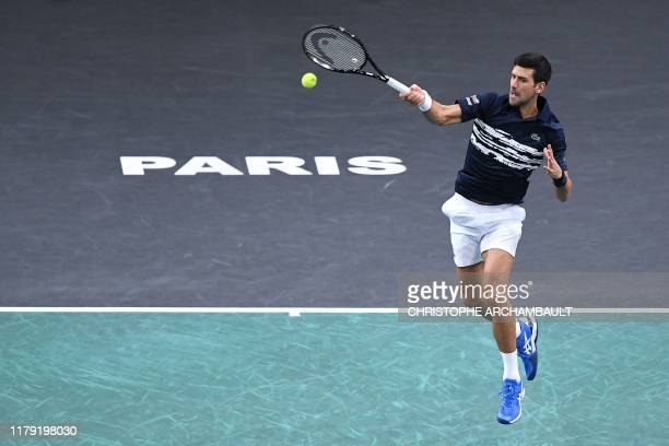Serbia's Novak Djokovic returns the ball to Britain's Kyle Edmund during their men's singles tennis match on day four of the ATP World Tour Masters...