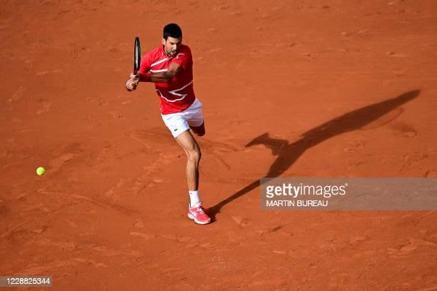 Serbia's Novak Djokovic returns the ball to Lithuania's Ricardas Berankis during their men's singles second round tennis match on Day 5 of The Roland...