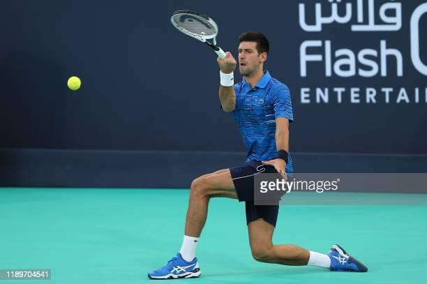 Serbia's Novak Djokovic returns the ball to Russia's Karen Khachanov during the Mubadala World Tennis Championship 3rd Place match at Zayed Sports...