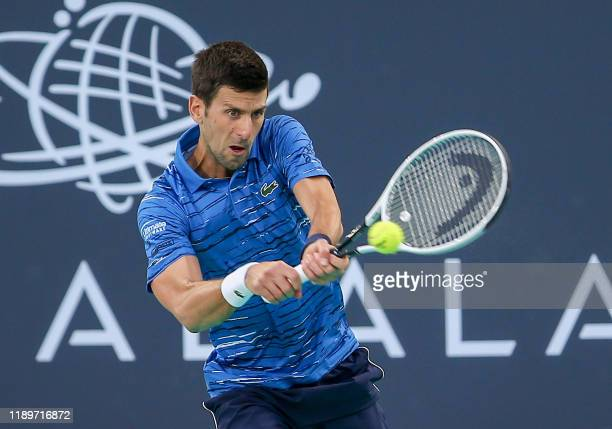 Serbia's Novak Djokovic returns the ball to Russia's Karen Khachanov during the Mubadala World Tennis Championship 3rd Place match at Zayed Sports...
