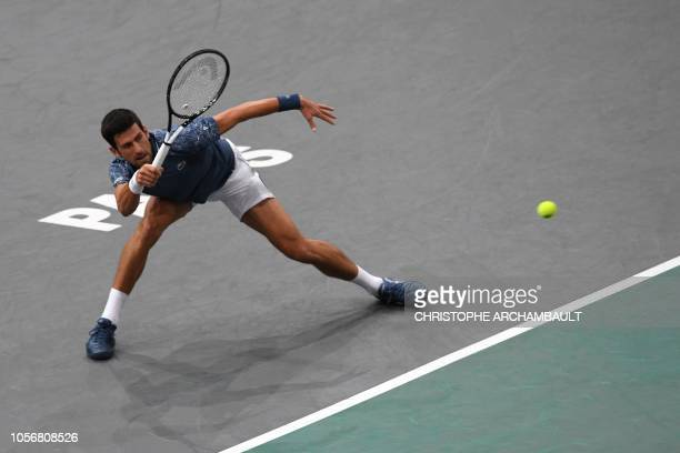 Serbia's Novak Djokovic returns the ball to Switzerland's Roger Federer during their men's singles semi-final tennis match on day six of the ATP...