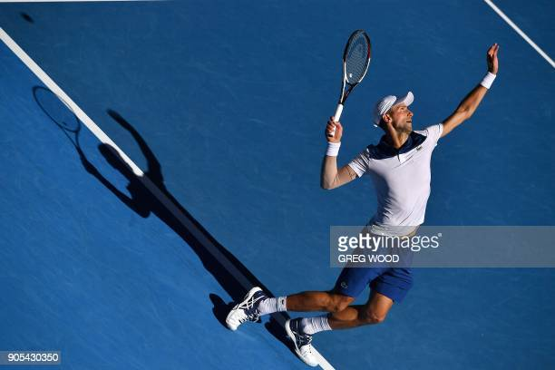 TOPSHOT Serbia's Novak Djokovic serves against Donald Young of the US during their men's singles first round match on day two of the Australian Open...