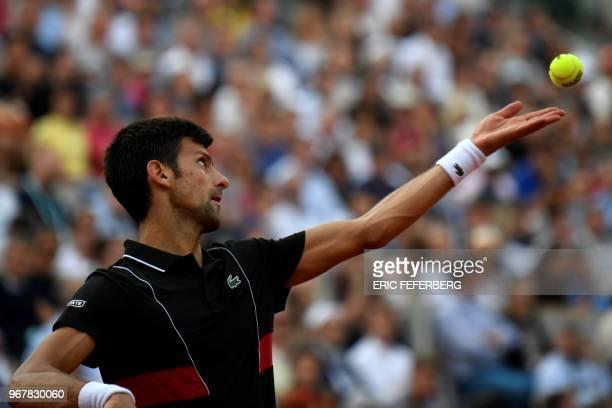 Serbia's Novak Djokovic serves to Italy's Marco Cecchinato during their men's singles quarterfinal match on day ten of The Roland Garros 2018 French...