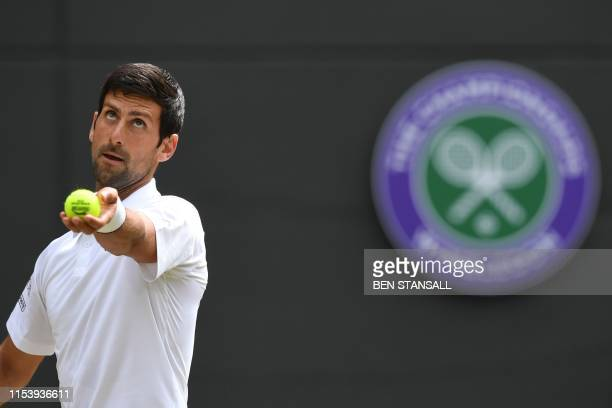 Serbia's Novak Djokovic serves to Poland's Hubert Hurkacz during their men's singles third round match on the fifth day of the 2019 Wimbledon...