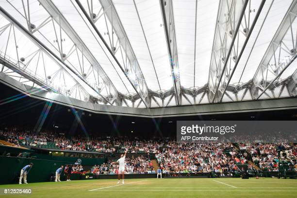 TOPSHOT Serbia's Novak Djokovic serves under the roof of centre court to France's Adrian Mannarino during their men's singles fourth round match on...