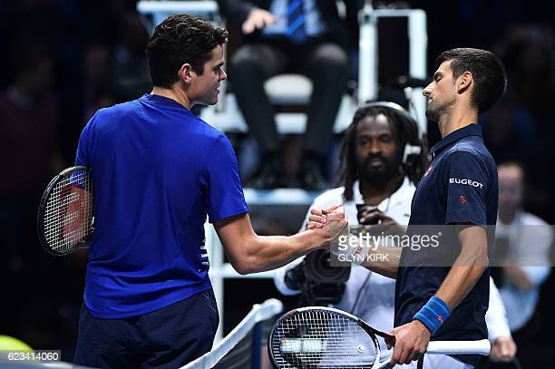 Serbia's Novak Djokovic shakes hands with Canada's Milos Raonic after winning their round robin stage men's singles match on day three of the ATP...