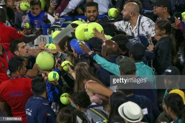 Serbia's Novak Djokovic signs autographs after losing to Greece's Stefanos Tsitsipas in their semi-final match of the Mubadala World Tennis...