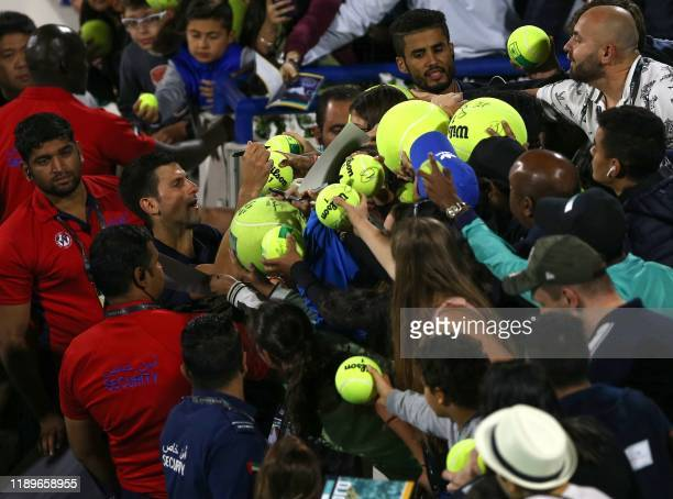 TOPSHOT Serbia's Novak Djokovic signs autographs after losing to Greece's Stefanos Tsitsipas in their semifinal match of the Mubadala World Tennis...