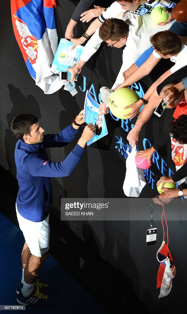 Serbia's Novak Djokovic signs autographs as he celebrates after victory in his men's singles final match against Britain's Andy Murray on day fourteen of the 2016 Australian Open tennis tournament in Melbourne on January 31, 2016.