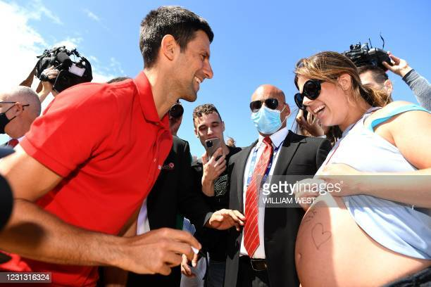 Serbia's Novak Djokovic signs on a pregnant woman Vanessa Kezerle's belly during a photo shoot for his winning the Norman Brookes Challenge Cup...