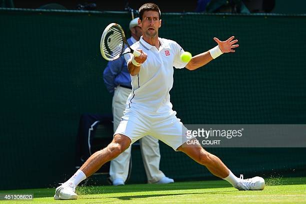 Serbia's Novak Djokovic slides on the grass as he returns against France's Gilles Simon during their men's singles third round match on day five of...