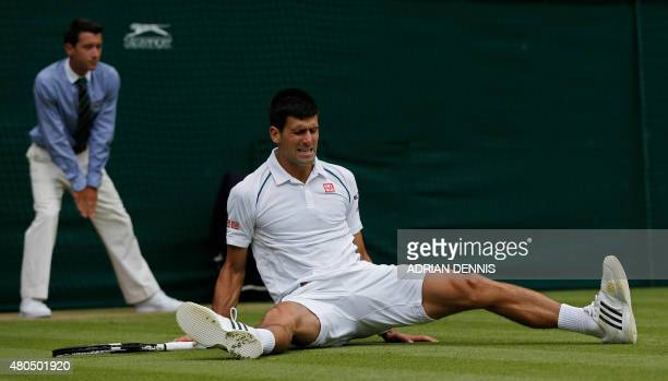 Serbia's Novak Djokovic slips on the grass after attempting to reach a return shot to Switzerland's Roger Federer during their men's singles final...