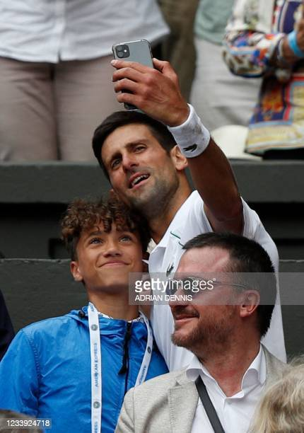 Serbia's Novak Djokovic takes a selfie with a fan after defeating Italy's Matteo Berrettini during their men's singles final match on the thirteenth...