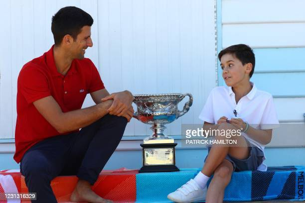 Serbia's Novak Djokovic talks to a boy Andrija Mihajlovic during a photo shoot with the Norman Brookes Challenge Cup trophy at the Brighton Beach in...
