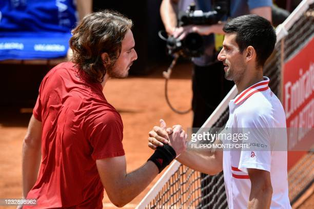 Serbia's Novak Djokovic taps hands with Greece's Stefanos Tsitsipas after winning their quarter final match of the Men's Italian Open at Foro Italico...
