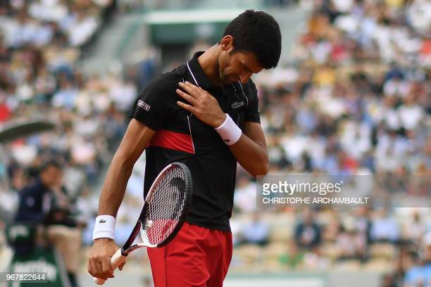 Serbia's Novak Djokovic touches his shoulder as he walks on court between points against Italy's Marco Cecchinato during their men's singles...