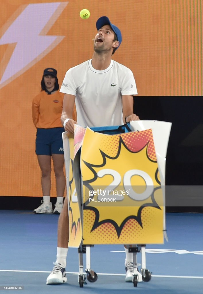 Serbia's Novak Djokovic (L) tries to catch balls in a basket during a Kids Day event ahead of the Australian Open tennis tournament in Melbourne on January 13, 2018. /
