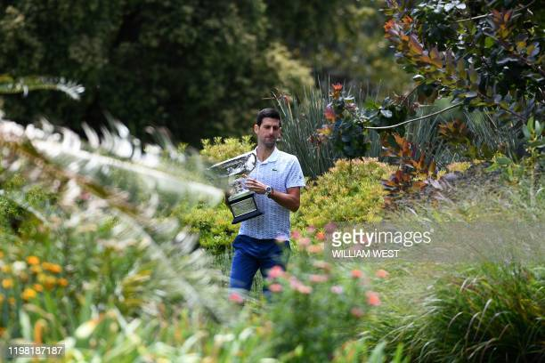Serbia's Novak Djokovic walks in the Royal Botanical Gardens with the Norman Brookes Challenge Cup trophy during a photo shoot in Melbourne on...
