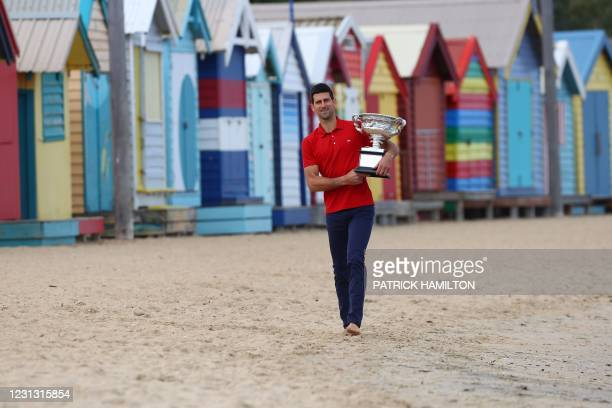 Serbia's Novak Djokovic walks on the Brighton Beach while holding the Norman Brookes Challenge Cup trophy during a photo shoot in Melbourne on...