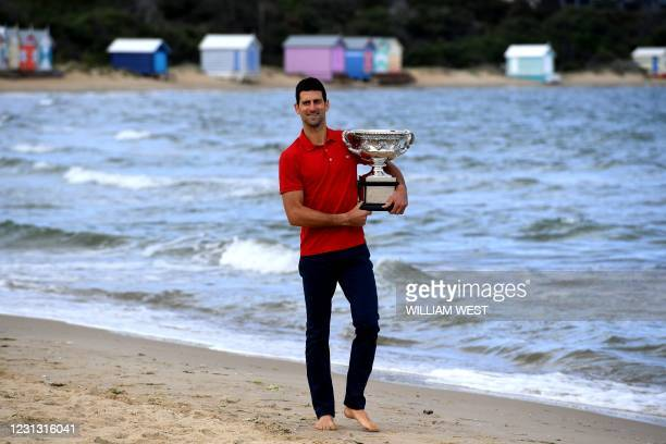 Serbia's Novak Djokovic walks on the Brighton Beach with the Norman Brookes Challenge Cup trophy during a photo shoot in Melbourne on February 22 a...