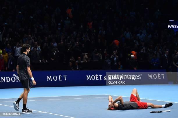 TOPSHOT Serbia's Novak Djokovic walks over to congratulate Germany's Alexander Zverev after he beats Djokovic in their men's singles final match on...