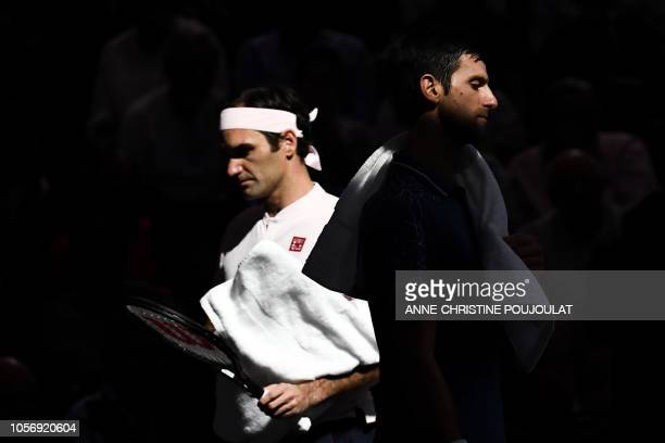 Serbia's Novak Djokovic walks past Switzerland's Roger Federer during a break, during their men's singles semi-final tennis match on day six of the...
