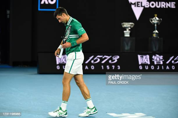 Serbia's Novak Djokovic walks with his racquet after smashing it as he plays against Germany's Alexander Zverev during their men's singles...