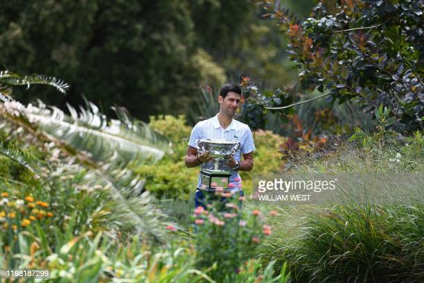 Serbia's Novak Djokovic walks with the Norman Brookes Challenge Cup trophy during a photo shoot in the Royal Botanical Gardens in Melbourne on...
