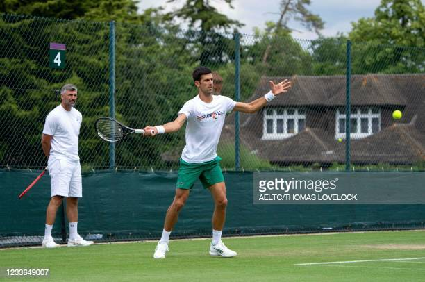 Serbia's Novak Djokovic, watched by coach Goran Ivanisevic takes part in a practice session at The All England Tennis Club in Wimbledon, southwest...