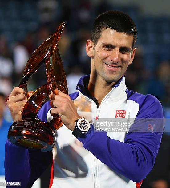 Serbia's Novak Djokovic, winner of the Mubadala World Tennis Championship, raises the trophy at the end of his match against Spain's Nicolas Almagro...