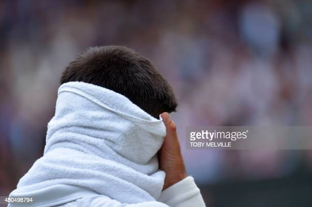 Serbia's Novak Djokovic wipes his head with a towel during a break in play against returns to Switzerland's Roger Federer during their men's singles...